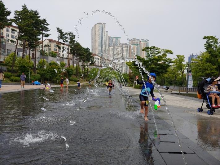 광교호수공원 바닥분수에서 아이들이 신나게 놀고 있다.